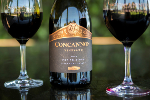 Concannon Vineyard Petite Sirah bottle with two glasses of wine